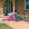 Cassandre Ulysse regarde ses filles faire des travaux de nettoyage dans une platebande de fleurs.