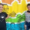 Deux femmes devant une murale colorée.