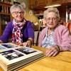 Deux femmes âgées regardent un album photo.