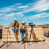 Le cinéaste Nicolas Lévesque est assis sur des planches de bois, un caméraman est à ses côtés.