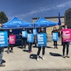 """Une dizaine d'employés tiennent des pancartes devant l'hôpital. L'une de ces affiches indique """"Bénin ou malin, nous sommes vitales""""."""