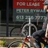 Un homme à vélo au centre-ville d'Ottawa porte un masque.