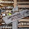 Une affiche en bois sur laquelle est inscrit savonnerie artisanale devant une étagère de savons.