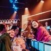Des jeunes entourent l'animateur de façon festive sur le plateau de l'émission 100 génies.
