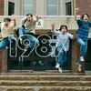 Quatre adolescents devant la porte d'une polyvalente sont pris en photo alors qu'ils sautent dans les airs.
