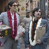Trois hommes en complets sombres avec des colliers de fleurs dans une rue en Inde, l'un la tête bandée