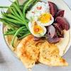 Un bol avec des œufs, de l'houmous, des fèves vertes, des betteraves rouges, du pita et un peu d'aneth.