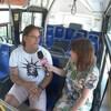 Il est dans un autobus et une femme tient un micro devant lui pour le passer en entrevue.