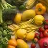 Une table recouverte d'asperges, de brocoli, de choux de Bruxelles, de fraises, de pommes et de tomates.