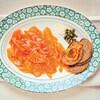 Une assiette contient de fines tranches de saumon, des oignons hachés, des câpres et des croûtons.