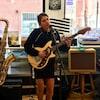 Laurence-Anne chante dans un micro et joue de la guitare. Au même moment, une saxophoniste joue de son instrument.