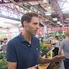 Jean-Philippe Cyr discute avec un journaliste dans un marché public.