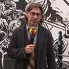 L'homme se tient devant une murale peinte en noir et blanc. Il tient son célèbre micro à l'effigie de l'émission Infoman. Le micro affiche un gros i rouge sur fond jaune et bleu.