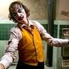 Dans une salle de bain sale et délabrée, un homme maquillé en clown (Joaquin Phoenix) esquisse un mouvement de danse.