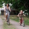 Une femme plus âgée, une jeune femme et une petite fille, sur une route de campagne, toutes les trois sur des vélos.