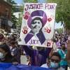 """Des personnes manifestent dans la rue. Au centre de la photo, une pancarte est tenue par une personne. La pancarte est une peinture qui montre la face de Joyce Echaquan, superposée sur un ruban mauve. Les mots """"Justice pour Joyce"""" sont également peints. Autour de la face de Joyce, des retrouve des traces de mains rouges, symbole de la lutte des femmes et filles autochtones disparues et assassinées."""