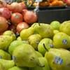Un présentoir de fruits avec des poires et des pommes grenades.