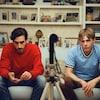 Deux jeunes hommes assis sur un canapé face à une caméra.