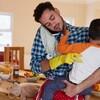 Un jeune père porte dans ses bras son petit garçon tout en faisant un appel sur son cellulaire, une de ses mains est gantée pour faire le ménage et à l'arrière, il y a la table de la cuisine avec déjeuner et toutou.
