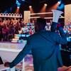 Il tient un parlophone dans ses mains et est de dos, sur le plateau de l'émission 100 génies.