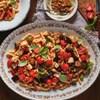 Un plat de pâtes avec des tomates, de l'aubergine, du basilic frais et des cubes de poisson.