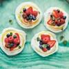 Un plateau avec quatre petites pâtisseries recouvertes de crème fouettée et de fruits.