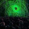 Dans une salle de spectacle du Planétarium de Montréal, des spectateurs regardent un film.