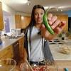 Cléa tient un piment vers la camera dans sa cuisine.