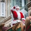 Le père Noel est sur son char et salue la foule