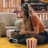 Assise par terre, Rosalie joue à la console vidéo.