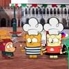 Ollie et Moon sont en Italie. Ils tiennent chacun un cornet de crème glacée et portent des toques de pâtissiers sur la tête. Ils discutent avec leurs amis.
