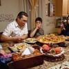 Fatine est assise à la table à manger avec sa famille. Ils mangent des repas Marocains.