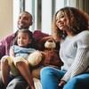 On voit un papa, une maman et leur fillette assis dans un canapé devant la télé en souriant.