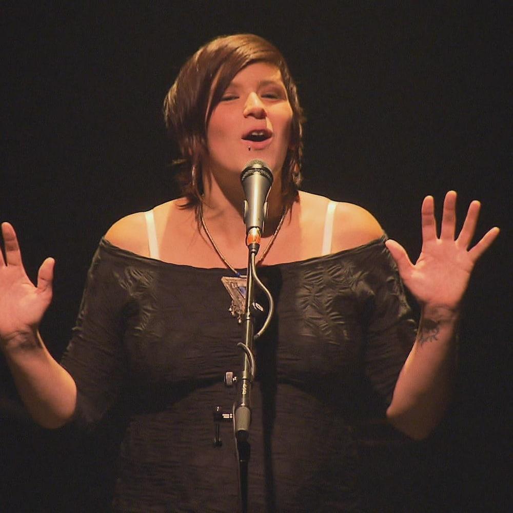 Marjolaine Beauchamp, enceinte et vêtue d'une robe noire, a les mains levées dans les airs pendant qu'elle livre un slam.
