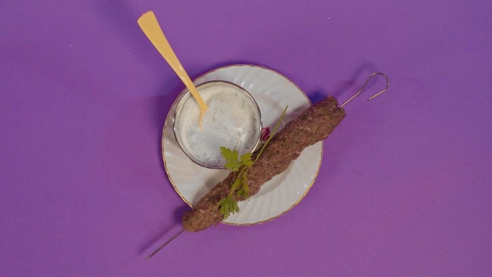 Une brochette de viande haché et une sauce blanche tzatziki.