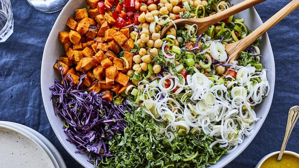 Salade colorée avec des poireaux hachés, des pois chiches, des poivrons rouges hachés, des patates douces et du choux rouge.