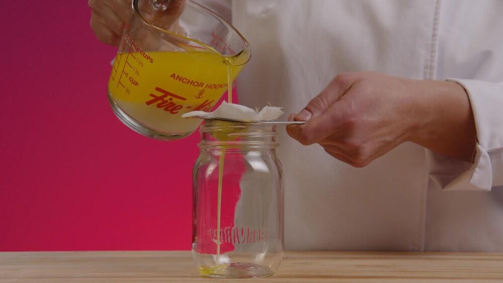 Une personne décante le beurre en versant uniquement le gras jaune dans un pot en verrre propre.