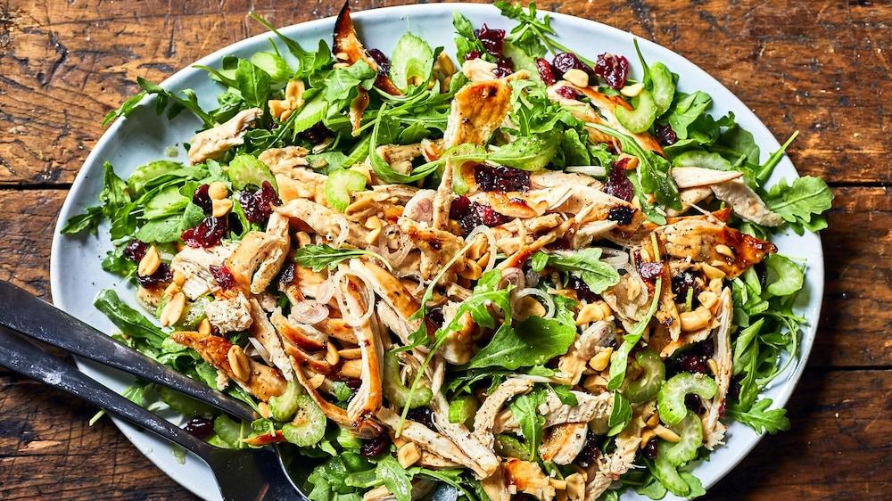 Une salade composée de roquette, de morceaux poulet grillés, des céleris coupés en rondelle et des canneberges séchées sont disposés dans une assiette ovale.