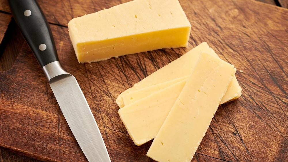 Un fromage à pâte ferme, tranché.