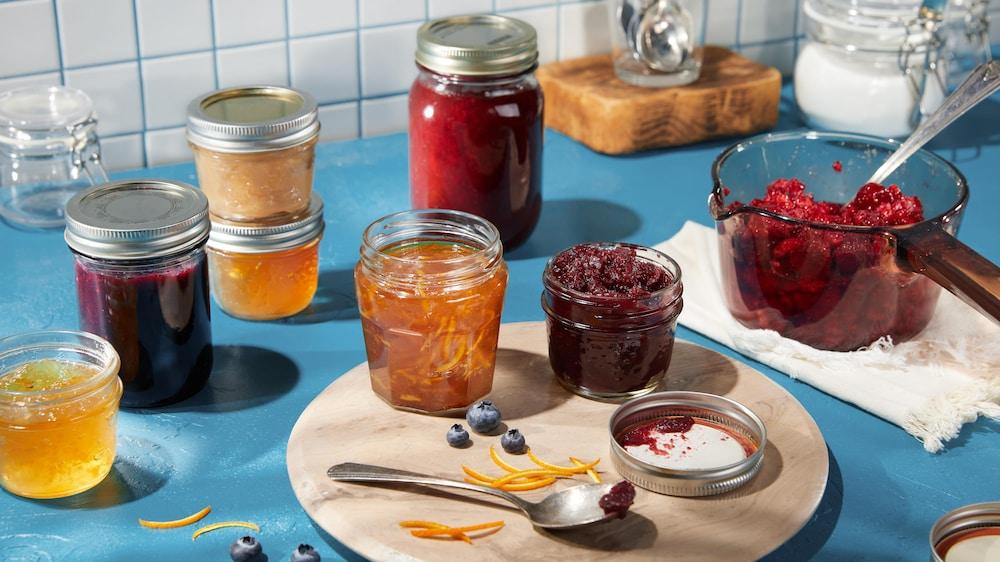 Des pots en verre remplis de plusieurs coulis aux fruits.