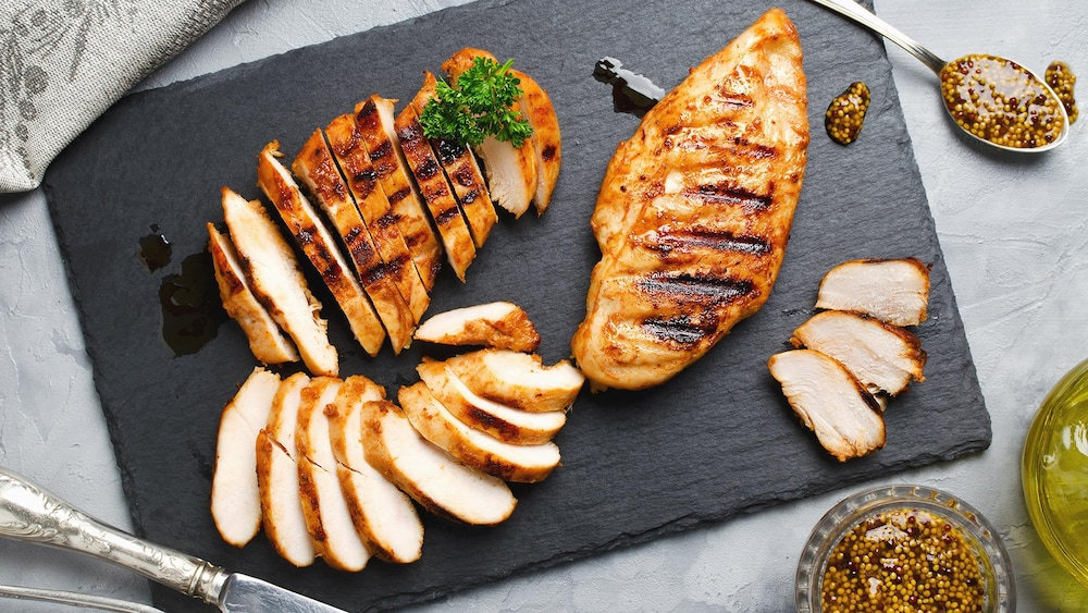 Des poitrines de poulet coupées en morceaux sur une planche à découper.