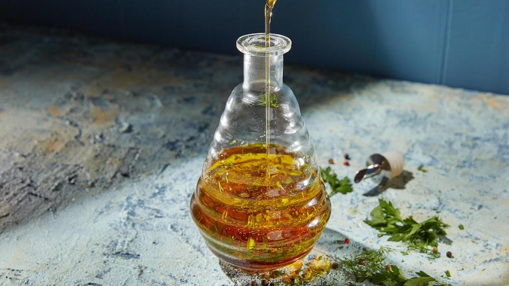 Un contenant en verre en train de se faire remplir de marinade.