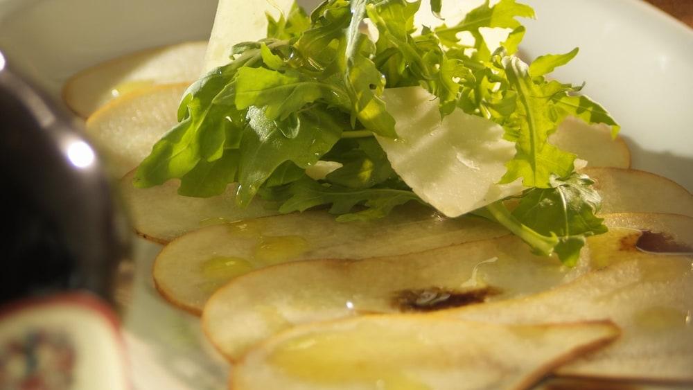 Carpaccio de poires bosc, salade de roquette dans une assiette.