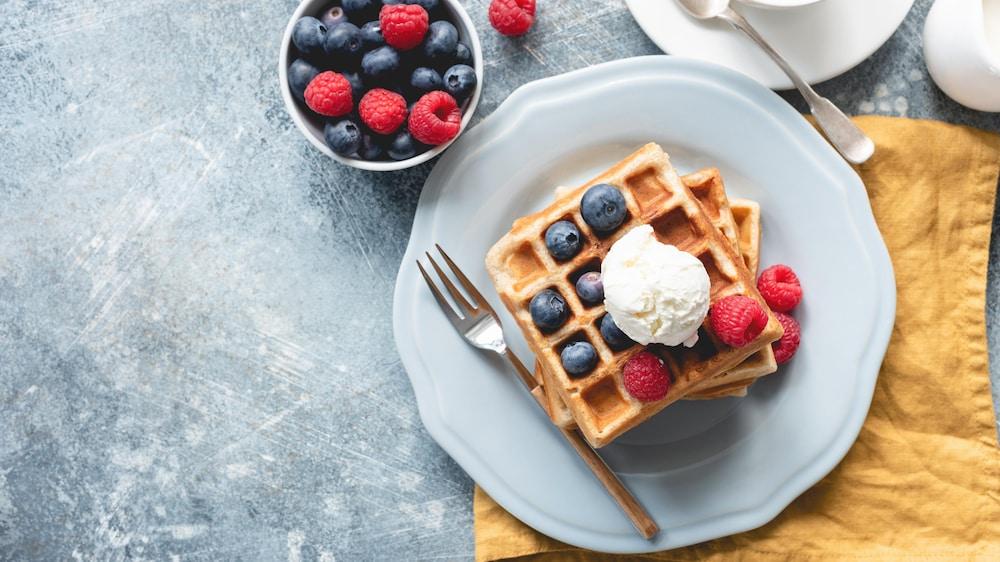 Trois gaufres dans une assiette avec une boule de crème glacée à la vanille, des framboises et des bleuets.