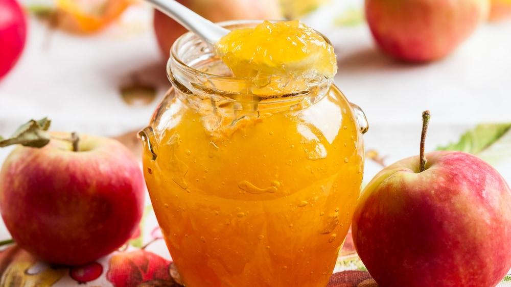 Un pot en verre rempli de gelée de pomme.