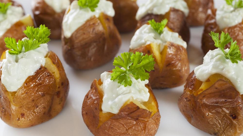 Plusieurs petites pommes de terre garnies de fromage.