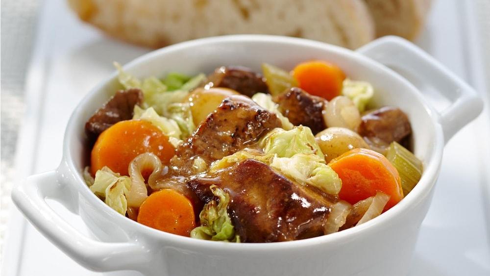 Un bol de mijoté de boeuf, de chou et de légumes, servi avec des tranches de pain croûté frais.