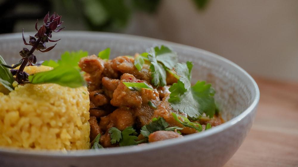 Un bol de cari rouge et de riz à l'ail garni d'herbes fraîches.