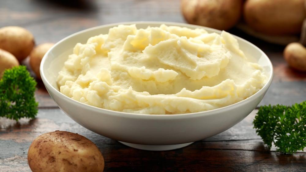 Un bol de purée de pommes de terre entouré de pommes de terre.