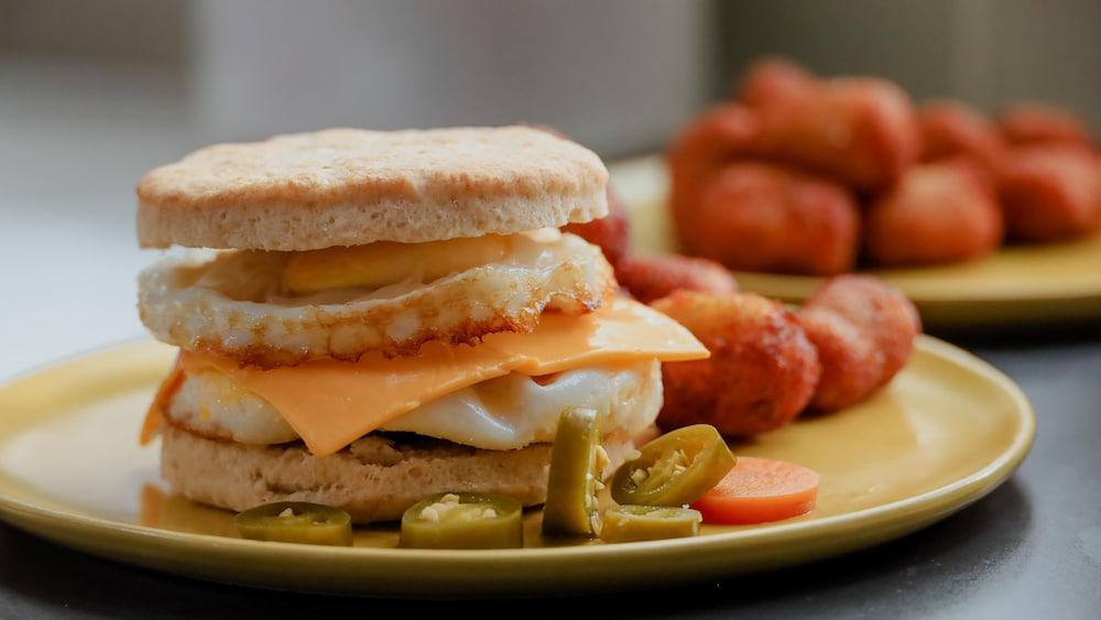Un sandwich déjeuner servi dans une assiette, aux côtés de pommes de terre déjeuner style hash brown et de piments forts marinés.